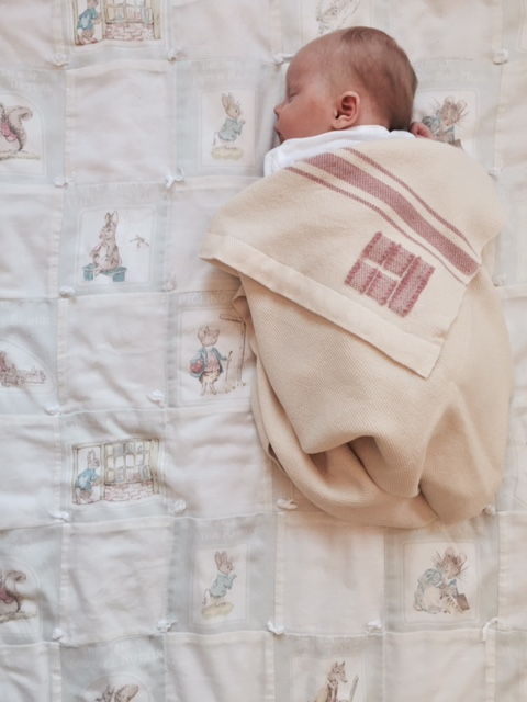 Campbell, in her Swans Island blanket on an heirloom Peter Rabbit blanket