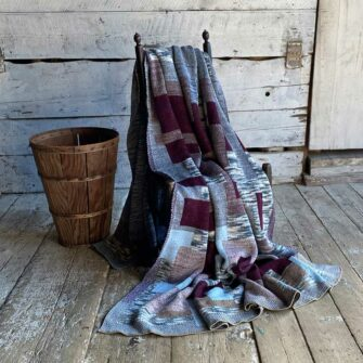 Artisan Patchwork Throw #23 is knit with a overall background of heathered greys and birch tones, with patchwork blocks in sky blue,  heathered maroon, burgundy, and grey tones.