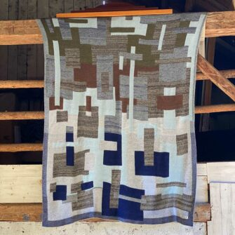 Swans-Island-Artisan-Patchwork-Throw-#21 knit in shades of heathered grey, sky blue, navy, brown and loden