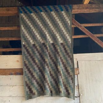 Swans Island Artisan Patchwork Throw #26 knit in USA in soft heathered greys and heathered lichen and brown tones, with patchwork blocks in denim blue, heathered cream, green, brown and, and azure blue tones.